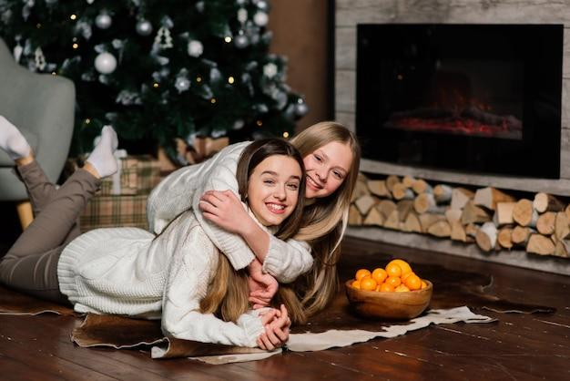 大晦日とクリスマスを祝い、ベッドでみかんを食べるガールフレンド。贈り物や金色のボールで飾られたモミの枝があります。