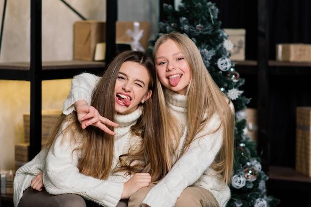 새해 이브와 크리스마스를 축하하고 침대에서 만다린을 먹는 여자 친구. 황금 공으로 선물과 장식 된 전나무 가지가 있습니다.