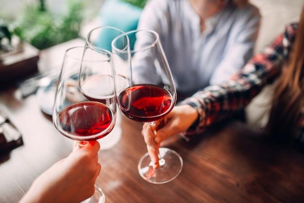 Подруги чокаются с красным вином