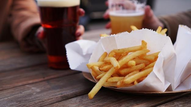 Подруги пьют пиво на фестивале уличной еды, картофель фри, нездоровая еда