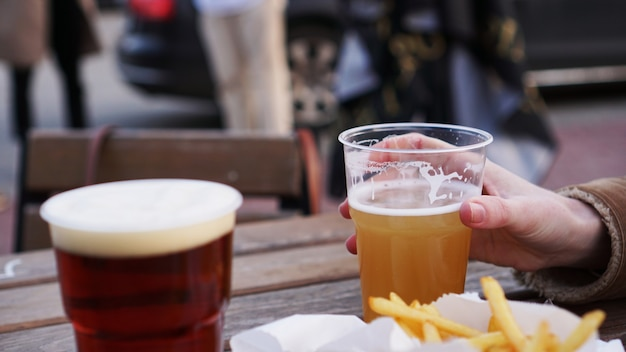 Girlfriends drink beer at the street food festival french fries unhealthy food