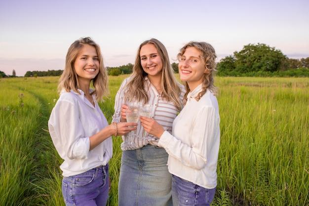 Подруги пьют шампанское на пикнике. женщины смеются и наслаждаются