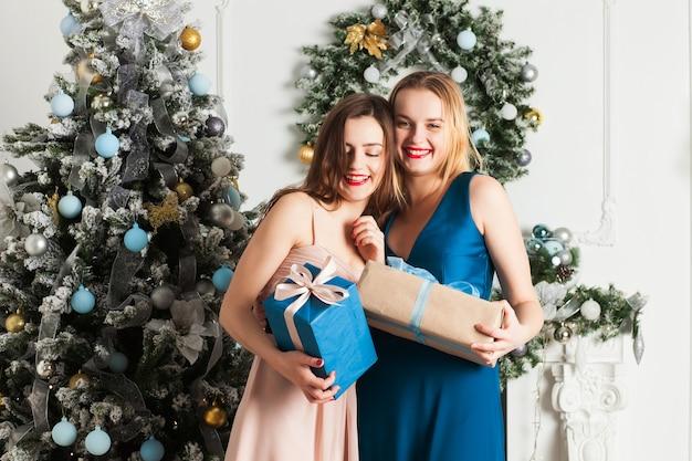 ガールフレンドはお互いにクリスマスプレゼントを贈ります。そして、受け取った贈り物を喜んでください。クリスマスツリーの隣。