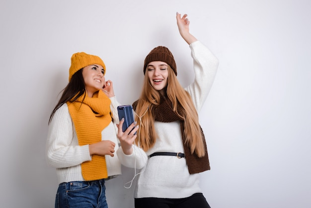 Girlfriends in hats and scarves listen to music