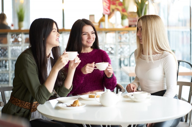 Girlfriends have a talk in cafe during teatime