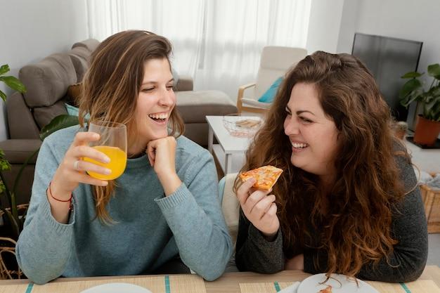 Fidanzate a casa che bevono succo di frutta