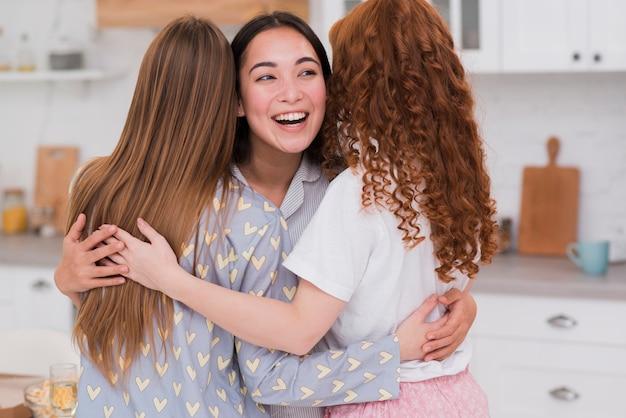 Girlfriends hugging on pijama party