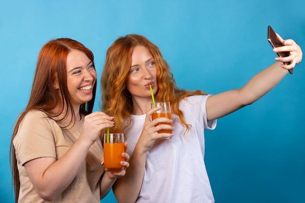 カジュアルな服装のガールフレンドはストローからジュースを飲み、自分撮りをします。青い壁に隔離。人々のライフスタイルの概念。