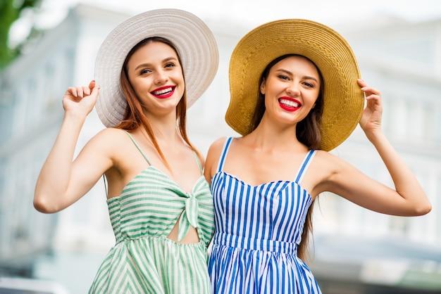 一緒にポーズをとる夏のドレスと麦わら帽子のガールフレンド