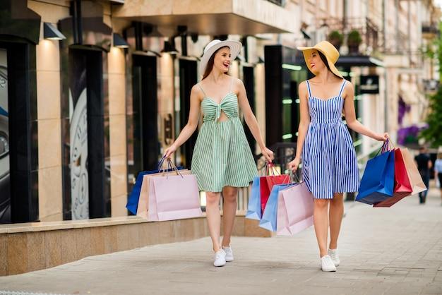 Подружки в летних платьях и соломенных шляпах позируют вместе