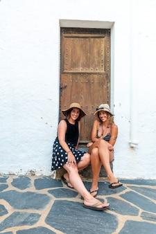 휴가를 즐기는 여름에 여자 친구입니다. 휴가에 더위를 즐기는 문 옆에 앉아 백인 여자