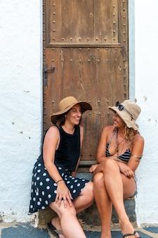 휴가를 즐기는 여름에 여자 친구입니다. 휴가철 더위를 즐기며 출입구에 앉아 웃고 있는 백인 소녀들