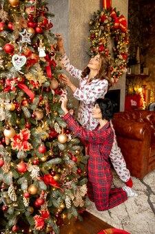 여자 친구는 크리스마스 전에 실내에서 크리스마스 트리를 장식하고 있습니다. 함께 시간 보내기