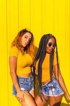 여자 친구의 라이프 스타일, 긴 머리 띠와 노란색 셔츠와 노란색 벽에 짧은 청바지에 금발 백인 흑인 소녀. 따뜻한 색감의 도시 세션