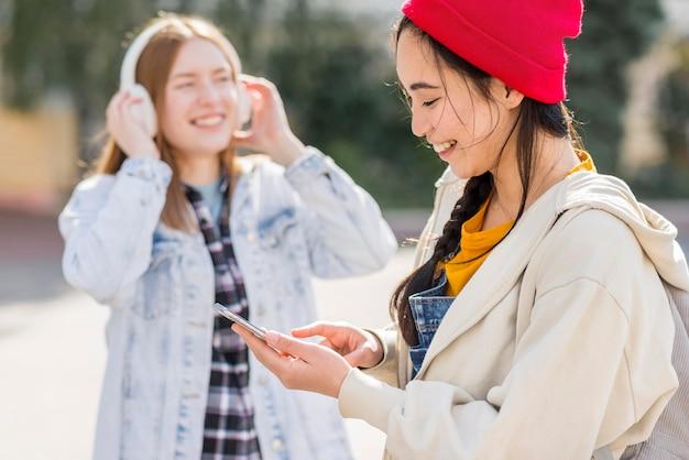 Girlfriends listening music at headphones