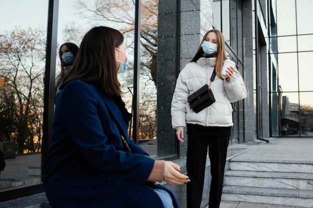 마스크를 착용하는 동안 커피에서 만나는 여자 친구