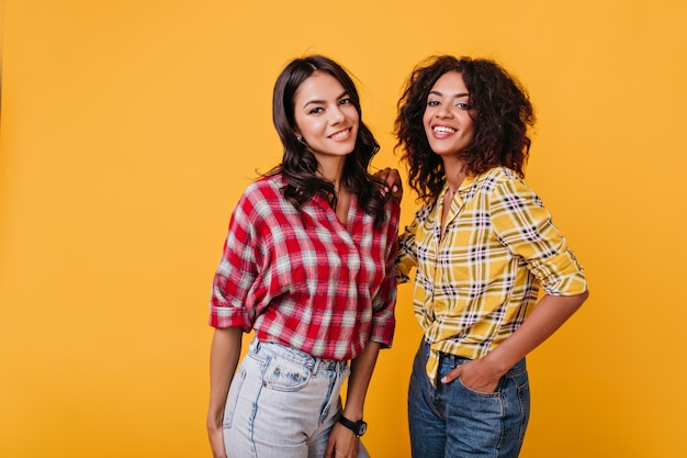 Подружки надевают такие же рубашки, чтобы мило выглядеть на фотосессии. портрет радостной брюнетки с карими глазами.