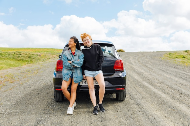 Girlfriends standing near car on road