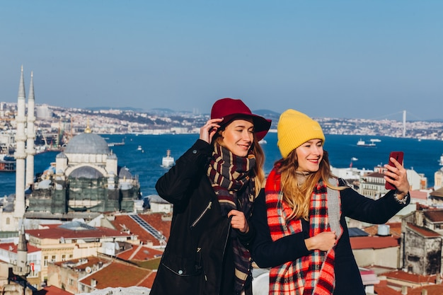 Girlfriends take a selfie on the roof of the grand bazaar, istanbul, turkey. two smiling girls are photographed on the phone against the background of istanbul on a clear winter day.