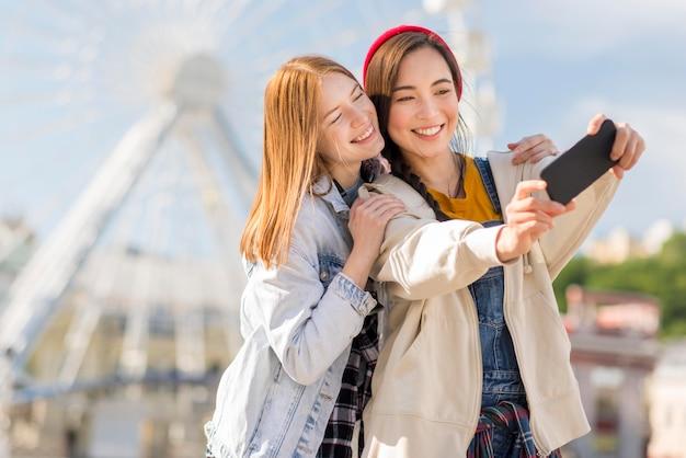 Amiche che prendono selfie all'occhio di londra
