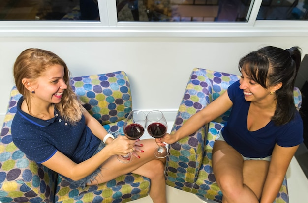 Подруги тосты с бокалами вина.