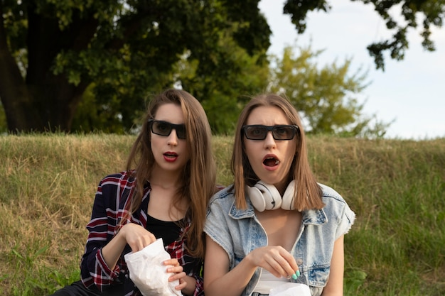 Girlfriends watch a movie in an outdoor movie theater.