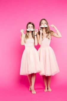 Girlfriends wearing in dresses having fun and sending kiss each other.
