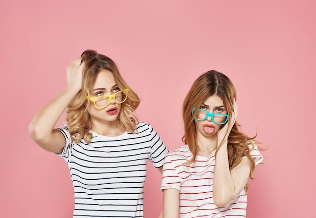 Girlfriends wearing sunglasses striped tshirts pink background communication