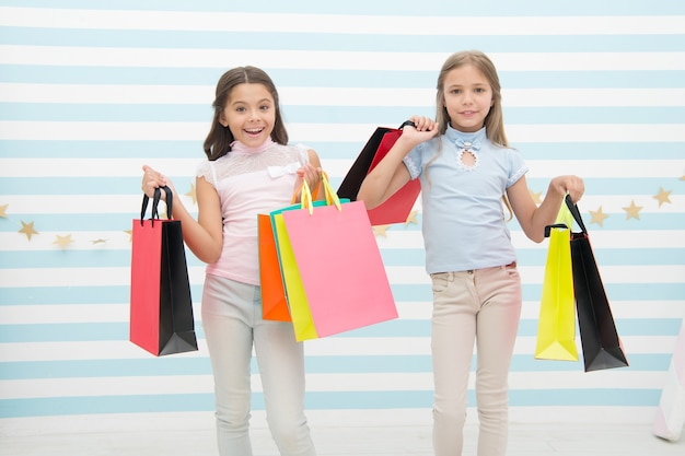 ガーリーな幸せ。子供たちは幸せな束のパッケージを運びます。親友のコンセプトで買い物。女の子は買い物が好きです。子供たち幸せな小さな女の子は買い物袋を持っています。親友や妹と一緒に買い物を楽しんでください。