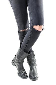 白で隔離される破れたジーンズで女の子らしい足