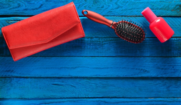 Girlish trend accessories on a blue wooden background. hairbrush, purse, bottle of perfume. copy space. top view.