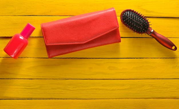 Girlish trend accessories on a yellow wooden background. hairbrush, purse, bottle of perfume. copy space. top view.
