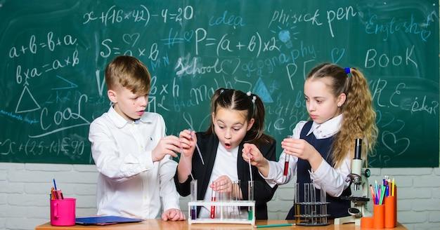 액체로 실험을 제공하는 소녀와 소년. 다채로운 액체 물질이 있는 시험관. 액체 상태 연구. 시험관을 가진 그룹 학교 학생들은 화학 액체를 연구합니다. 과학 개념입니다.