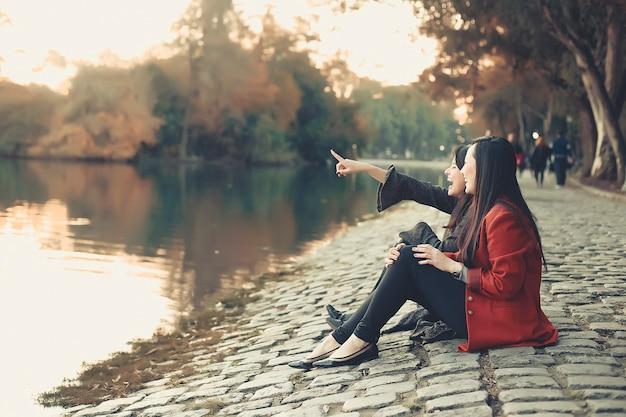 Девушки и подруги сидят в парке