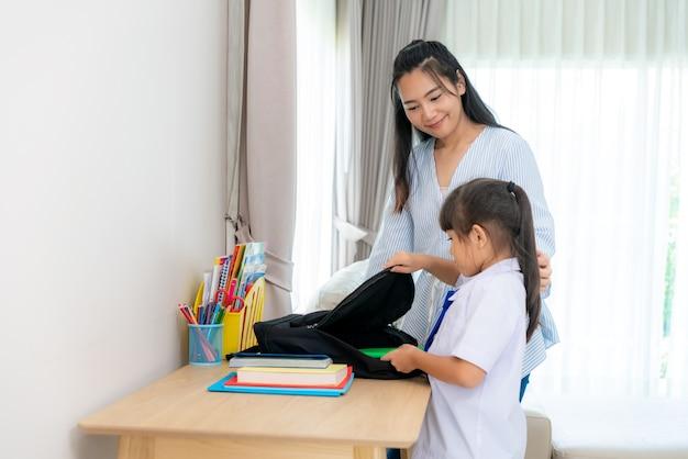 女の子と彼女の母親は、学校の初日を準備して、ランドセルを梱包しています。