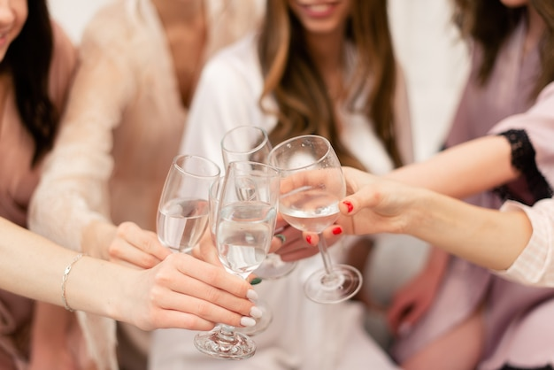 The girls are celebrating the bride's bachelorette party. the girls clink glasses of wine.