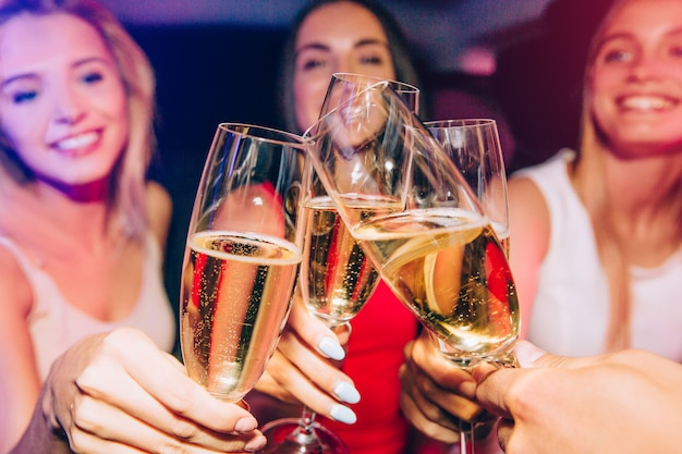 Girls are clinking with glasses of champagne