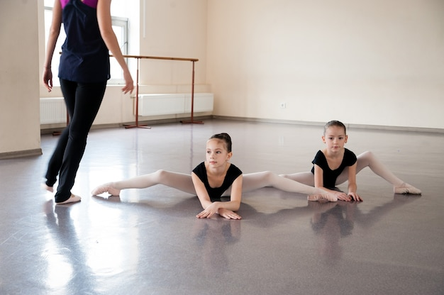 Девочки занимаются хореографией в балетном классе. Premium Фотографии