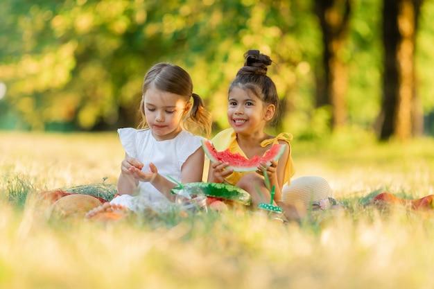 女の子は公園の毛布に座ってスイカを一枚食べる子供たちは屋外で果物を食べる