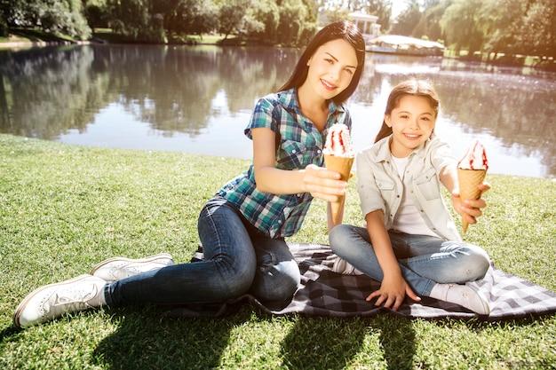 Девушки сидят на одеяле возле воды и позируют. они держат минусы мороженого и смотрят на камеру. они улыбаются. на улице солнечно в парке.