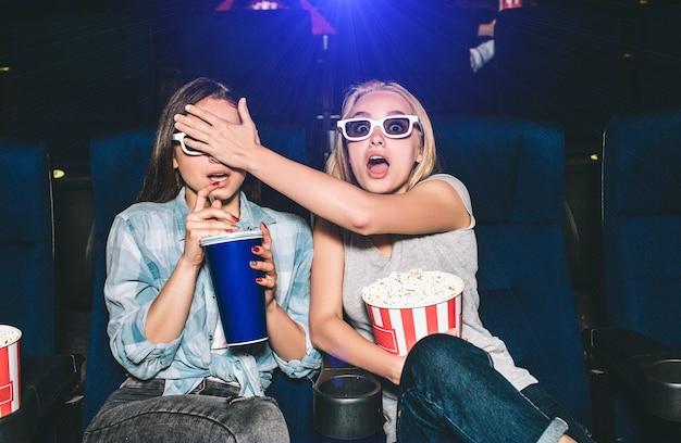 Девочки в ужасе. они смотрят фильм ужасов. блондинка закрывает глаза подруге. брюнетка пытается выпить колы из большой чашки