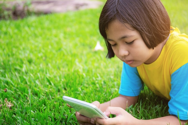 Girls are using tablet on lawn.