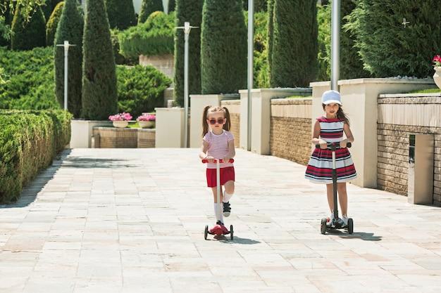晴れた日の女の子。屋外でスクーターに乗る未就学児の女の子。通りで遊んで幸せなかわいい小さな子供たち