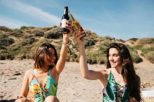 Девушки на пляже тосты с пивом