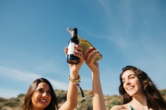 Girls at the beach toasting with beer