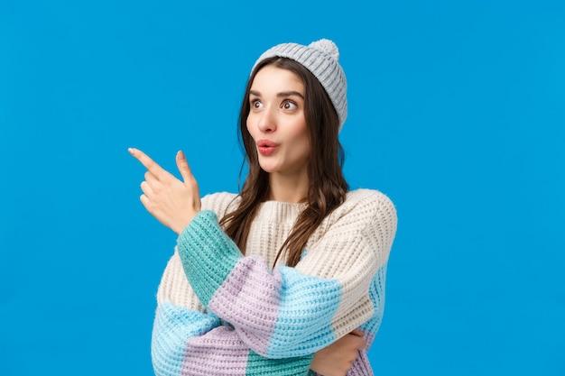 Внимание девушек привлекло что-то интересное, что происходило поблизости. заинтригованная, любопытная красивая брюнетка в зимнем свитере, шляпе, смотрящая влево со сложенными губами, изумленная, синий фон