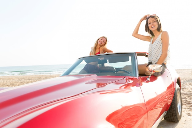 Girls at beach in sports car convertible having