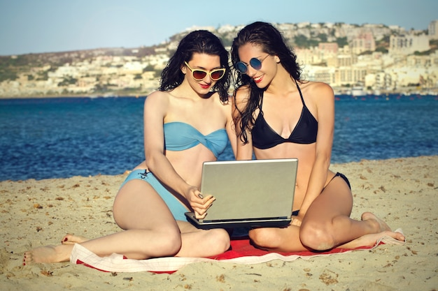 Girls on the beach with a laptop