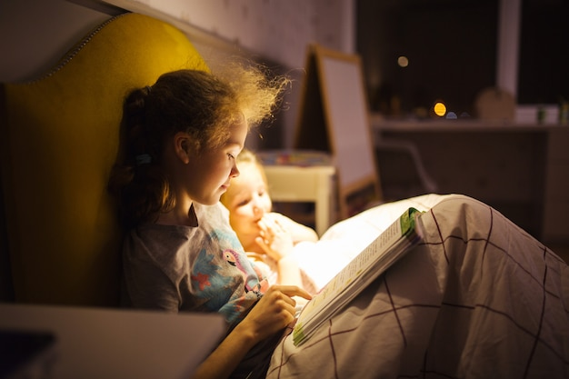 Girls best friends read fairy tale before sleep. best books for kids. sisters read book in bed. family tradition.