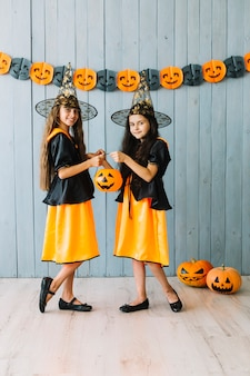 Girls in black and orange dresses holding halloween basket